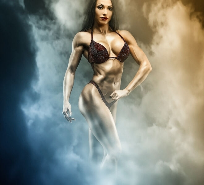 Strong and muscular sports girl in bikini posing against camera